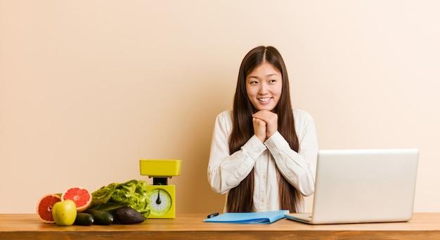 La giovane donna cinese del nutrizionista che lavora con il suo computer portatile tiene le mani sotto il mento, sta guardando felicemente da parte.