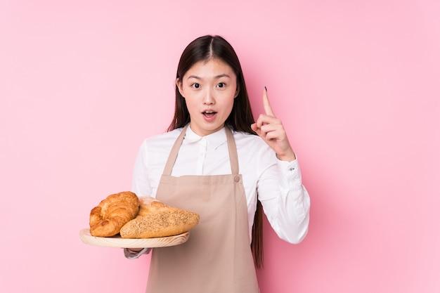 La giovane donna cinese del panettiere ha isolato avendo un'idea, concetto di ispirazione.