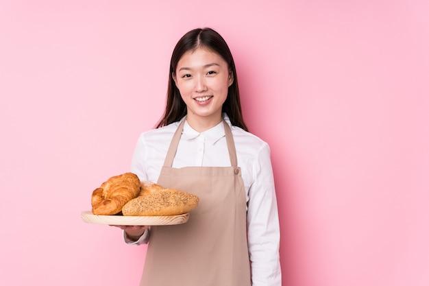La giovane donna cinese del panettiere ha isolato felice, sorridente e allegro.