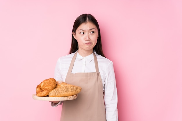 La giovane donna cinese del panettiere isolata confusa, si sente dubbiosa e incerta.