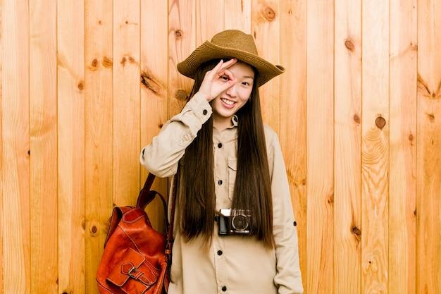 La giovane donna cinese del viaggiatore ha eccitato mantenendo il gesto giusto sull'occhio.