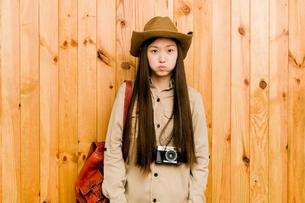 La giovane donna cinese del viaggiatore soffia sulle guance, ha un'espressione stanca
