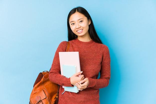 La giovane donna cinese dello studente ha isolato felice, sorridente e allegro.