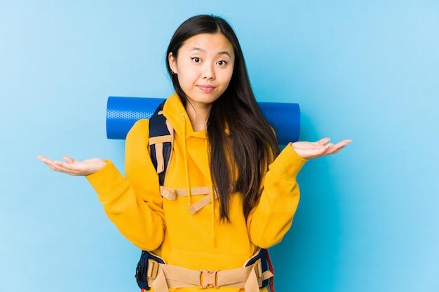 La giovane donna cinese di viaggiatore con zaino e sacco a pelo ha isolato dubitare e scrollare le spalle le spalle nel gesto interrogante.