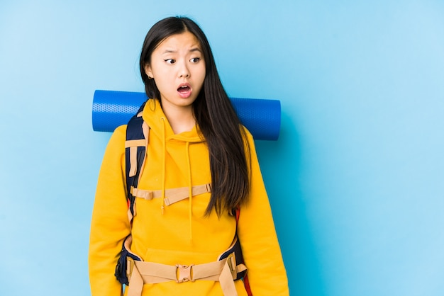 La giovane donna cinese di viaggiatore con zaino e sacco a pelo ha isolato essere colpito a causa di qualcosa che ha visto.