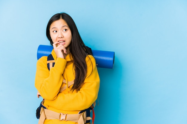 La giovane donna cinese di viaggiatore con zaino e sacco a pelo ha isolato il pensiero rilassato a qualcosa che esamina uno spazio della copia.