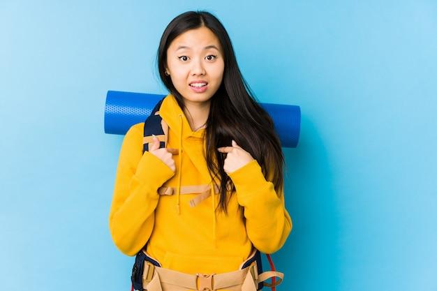 La giovane donna cinese di viaggiatore con zaino e sacco a pelo ha isolato indicare sorpreso con il dito, sorridendo ampiamente.