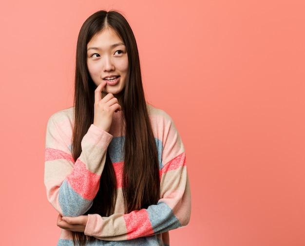 La giovane donna cinese fresca si è distesa pensando a qualcosa che esamina uno spazio della copia.