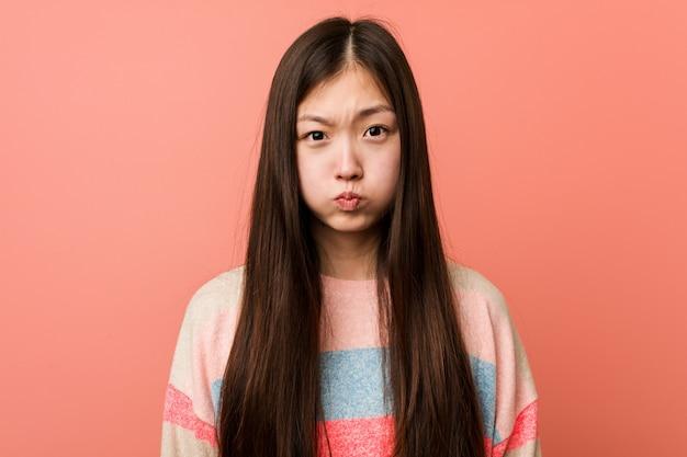 La giovane donna cinese fresca soffia le guance, ha un'espressione stanca. concetto di espressione facciale.