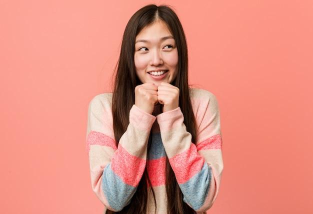 La giovane donna cinese fresca tiene le mani sotto il mento, sta guardando felicemente da parte.