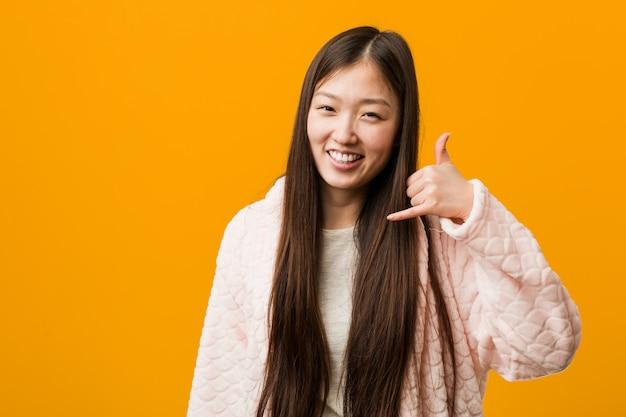 La giovane donna cinese in pigiama che mostra un telefono cellulare chiama il gesto con le dita.