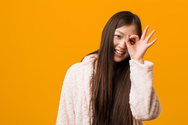 La giovane donna cinese in pigiama ha eccitato mantenendo il gesto giusto sull'occhio.