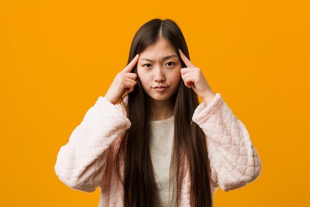 La giovane donna cinese in pigiama ha messo a fuoco su un compito, mantenente gli indici che indicano la testa.