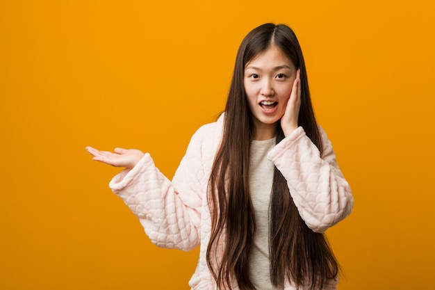 La giovane donna cinese in pigiama tiene lo spazio della copia su una palma, tiene per mano la guancia. stupito e felice.