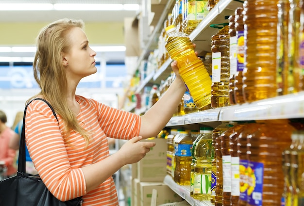 La giovane donna compra l'olio di girasole