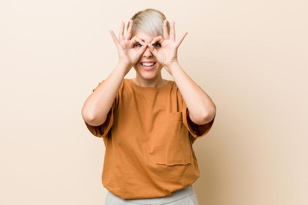 La giovane donna con i capelli corti che mostra bene firma sopra gli occhi