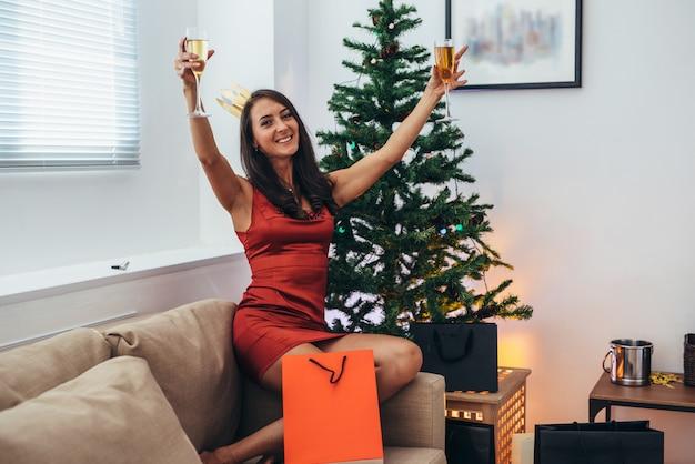 La giovane donna con i sacchetti della spesa si avvicina all'albero di natale.