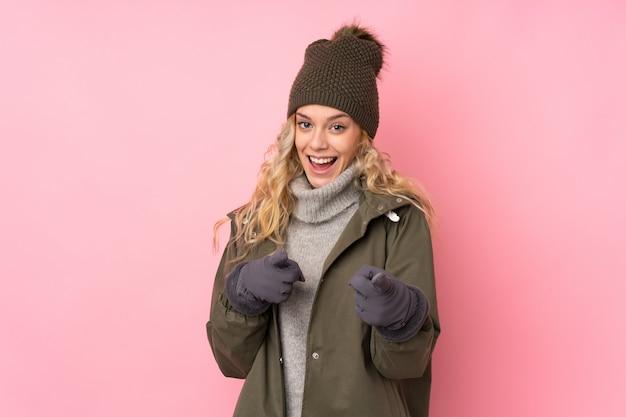 La giovane donna con il cappello dell'inverno isolato sulla parete rosa indica il dito voi