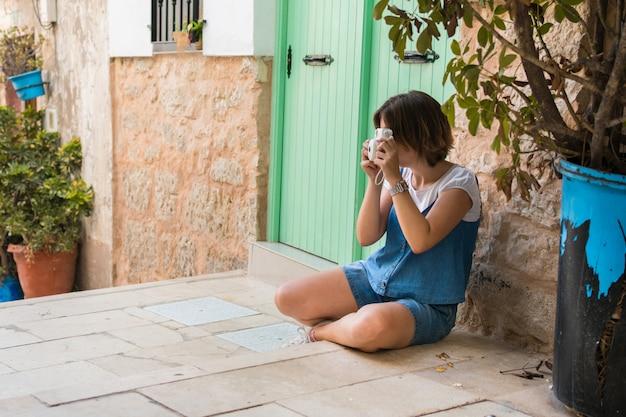 La giovane donna con la macchina fotografica istantanea sta sedendosi sulla via