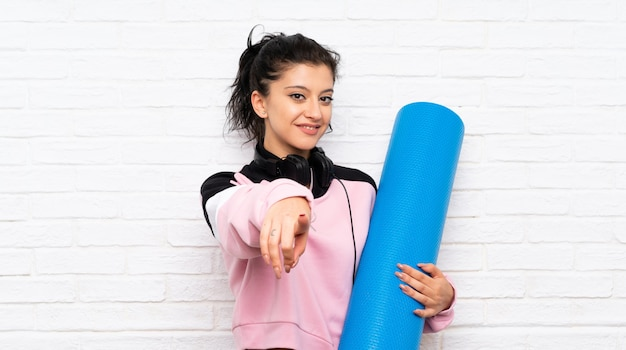 La giovane donna con la stuoia sopra il muro di mattoni bianco indica il dito con un'espressione sicura
