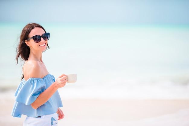 La giovane donna con la tazza di caffè caldo gode delle feste