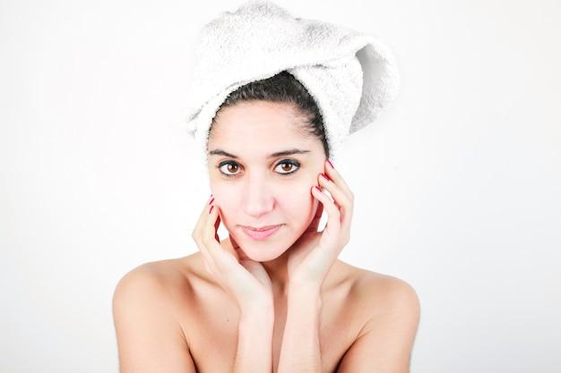 La giovane donna con un asciugamano ha avvolto la sua testa contro fondo bianco