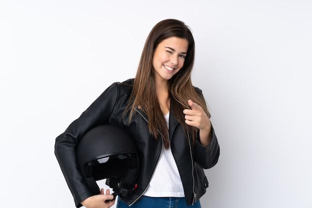 La giovane donna con un casco del motociclo sopra la parete bianca isolata indica il dito voi