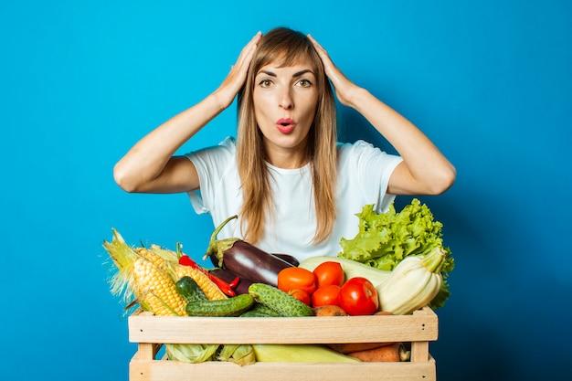 La giovane donna con un fronte sorpreso tiene una scatola con gli ortaggi freschi sul blu. buon concetto di vendemmia, prodotto naturale