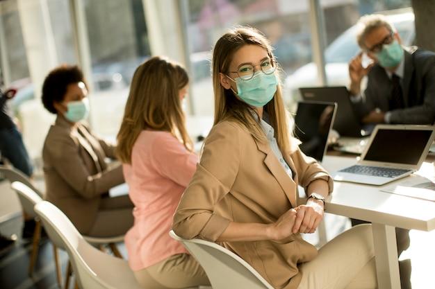 La giovane donna con un gruppo di uomini d'affari ha una riunione e lavora in ufficio e indossa una maschera come protezione dal virus corona