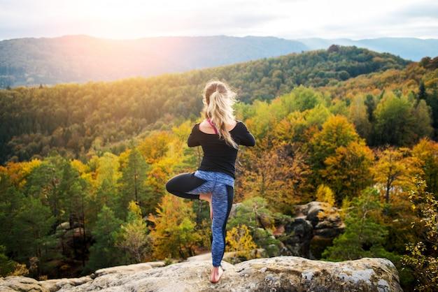 La giovane donna concentrata sta praticando yoga sulla cima della montagna la sera
