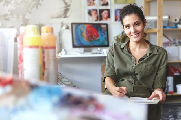 La giovane donna creativa positiva si è vestita casualmente, sedendosi nel suo laboratorio, facendo schizzi con la matita, essendo coinvolta nel processo creativo, godendo del suo lavoro. concetto di persone, stile di vita e arte