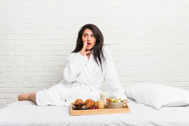 La giovane donna curvy che fa una colazione sul letto sta dicendo una notizia di frenata calda segreta e sta guardando da parte