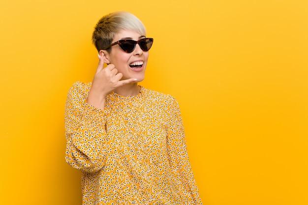 La giovane donna curvy che indossa un'estate floreale copre la mostra del gesto di chiamata di un telefono cellulare con le dita.