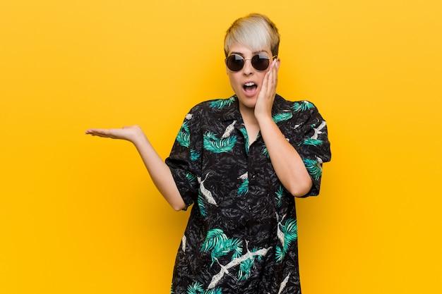 La giovane donna curvy che porta un sembrare dell'estate tiene lo spazio della copia su una palma, tiene per mano la guancia. stupito e felice.