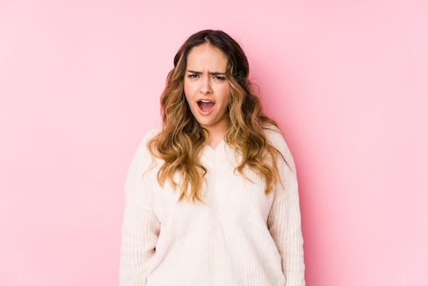 La giovane donna curvy che posa in una parete rosa ha isolato le grida molto arrabbiate e aggressive.