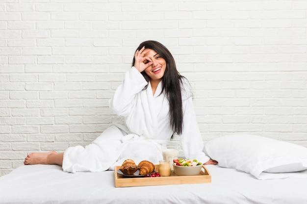 La giovane donna curvy che prende una prima colazione sul letto ha eccitato mantenendo il gesto giusto sull'occhio.