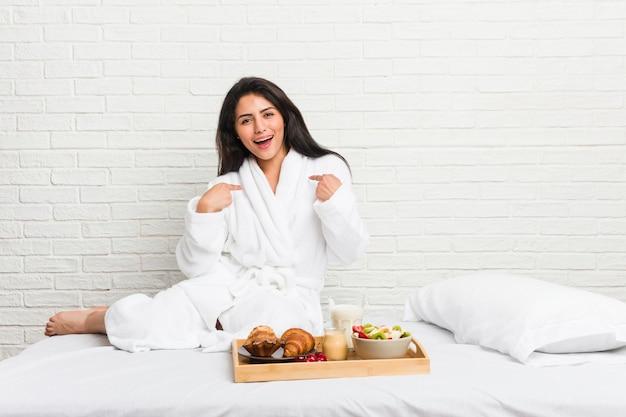 La giovane donna curvy che prende una prima colazione sul letto ha sorpreso indicare con il dito, sorridendo ampiamente.