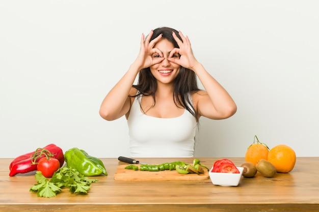 La giovane donna curvy che prepara un pasto sano che mostra bene firma sopra gli occhi
