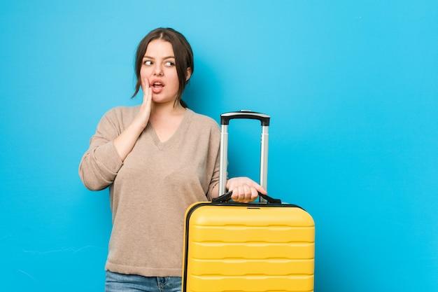 La giovane donna curvy che tiene una valigia sta dicendo una notizia di frenata calda segreta e sta guardando da parte