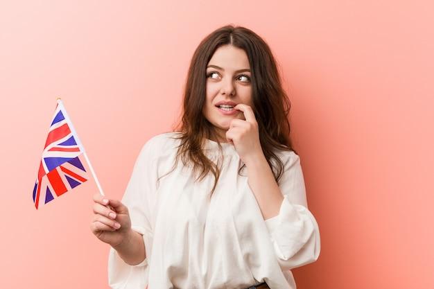 La giovane donna curvy di dimensione più che tiene una bandiera del regno unito ha rilassato il pensiero circa qualcosa che esamina uno spazio della copia.