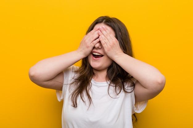 La giovane donna curvy plus size copre gli occhi con le mani, sorride ampiamente aspettando una sorpresa.
