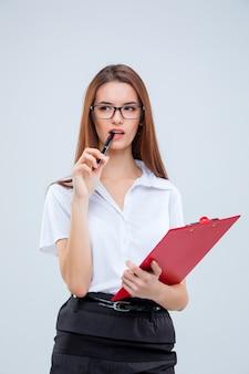 La giovane donna d'affari con penna e tablet per le note sulla parete grigia