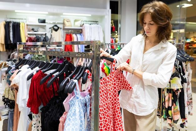 La giovane donna dai capelli castani sceglie il vestito estivo al negozio di abbigliamento