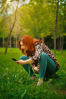 La giovane donna dai capelli rossi gode della fotografia mobile nel parco