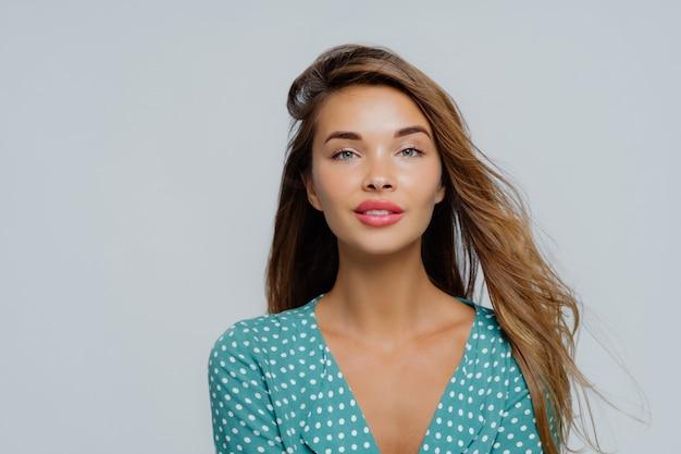 La giovane donna dall'aspetto piacevole guarda con calma la macchina fotografica, ha i capelli lunghi, vestita in camicia a pois