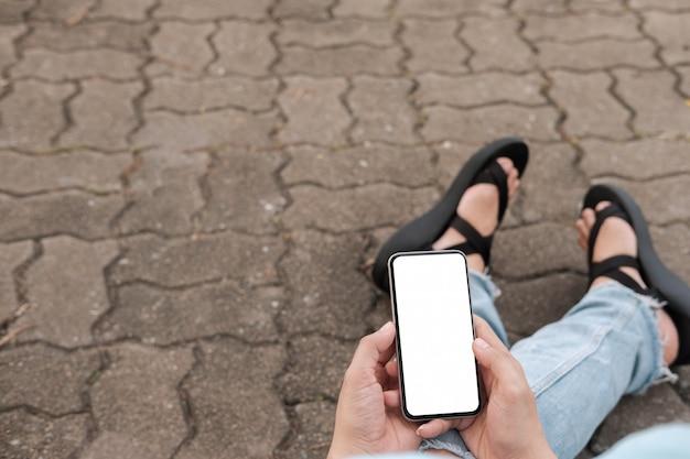 La giovane donna dei pantaloni a vita bassa della mano facendo uso dello smart phone sulla strada del mattone