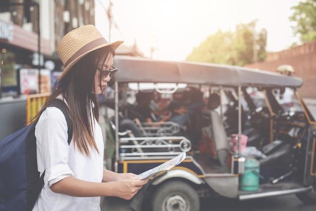 La giovane donna dei viaggiatori con lo zaino che guarda tiene una mappa alla capitale. giorno del turismo