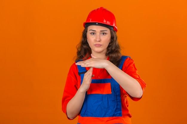 La giovane donna del costruttore in uniforme della costruzione ed il casco di sicurezza che sembrano sovraccarico fare il gesto di time out sopra la parete arancio isolata