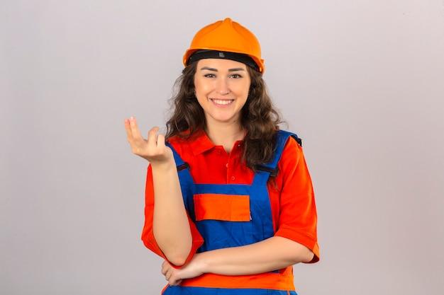 La giovane donna del costruttore nell'uniforme della costruzione e nel casco di sicurezza che sorride la presentazione e l'invito a venire con consegnano la parete bianca isolata