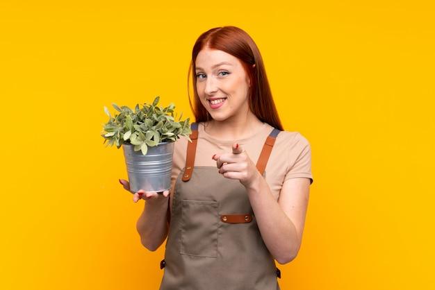 La giovane donna del giardiniere della testarossa che tiene una pianta sopra giallo isolato indica il dito voi